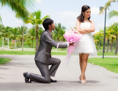 A man on one knee and giving flowers to girl